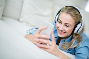 Woman listening to music at home on her cell phone and using headphones